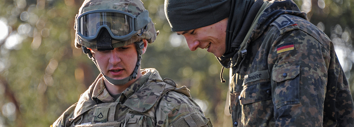 A U.S. Soldier, left, with 2nd Cavalry Regiment and a German soldier familiarize with each others equipment as part of exercise Dynamic Front 18 at the 7th Army Training Command's Grafenwoehr training area, Germany, March 8, 2018. Exercise Dynamic Front 18 includes approximately 3,700 participants from 26 nations at the U.S. Army's Grafenwoehr Training Area (Germany), Feb. 23-March 10, 2018.